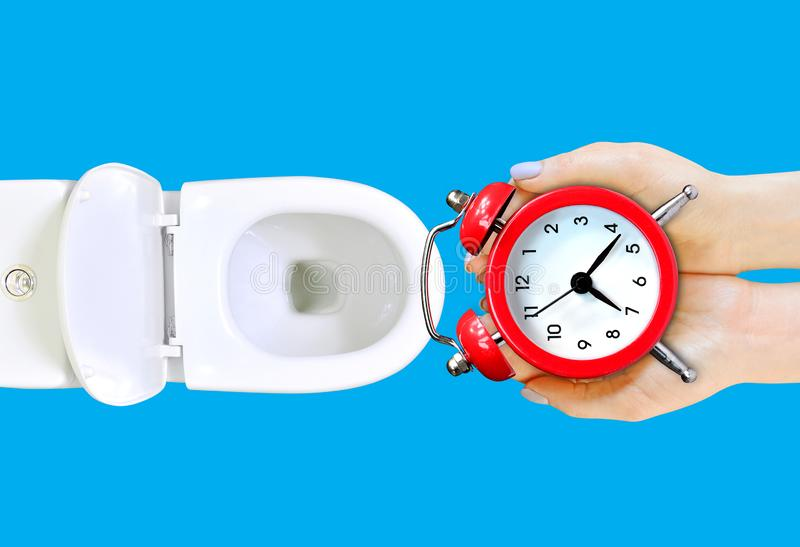 Do not waste your time advice.  The girl is going to throw the alarm clock in the toilet. Wasting time concept. Isolated on blue, copy space stock photography