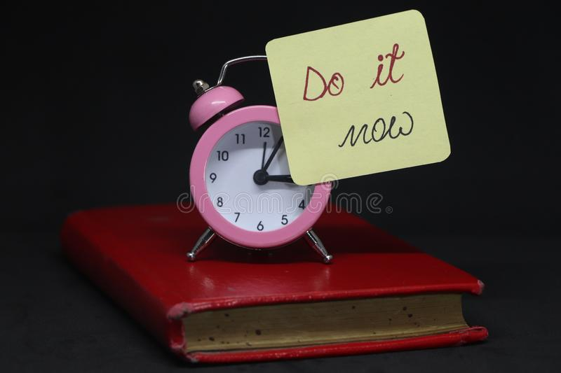 Do it now!. Do it now! on alarm clock on red book royalty free stock photos