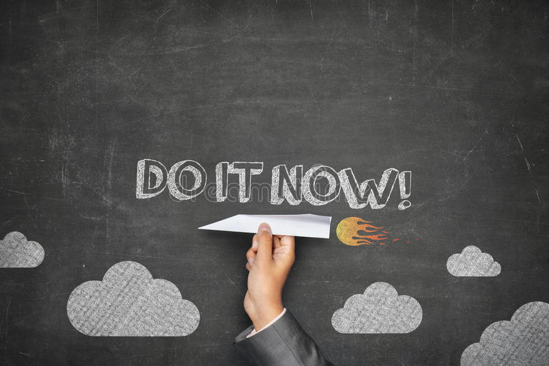 Do it now concept. On black blackboard with businessman hand holding paper plane royalty free stock photography