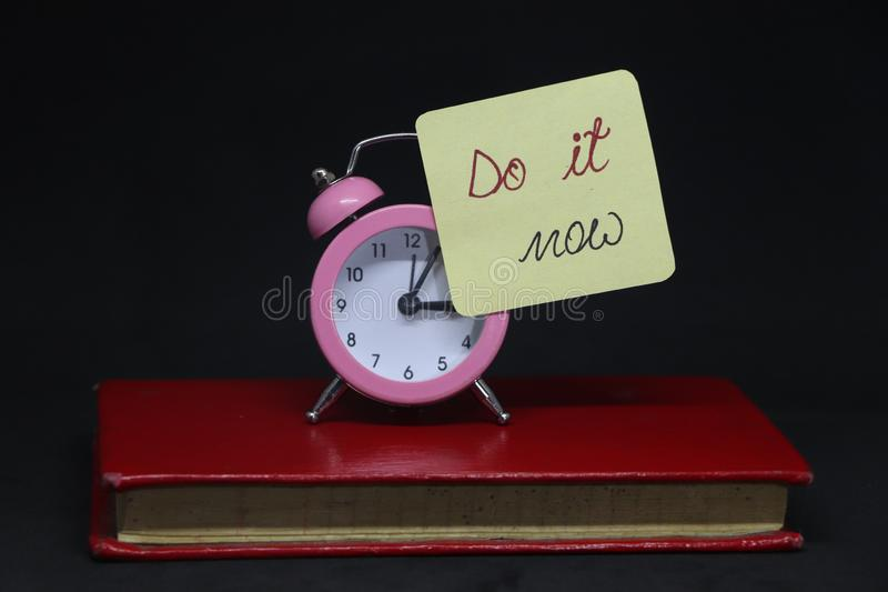Do it now. Do it now! Note on alarm clock on red book stock photo