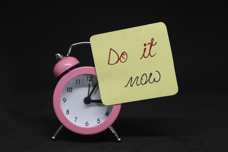 Do it now. Do it now! Note on alarm clock on red book royalty free stock photo