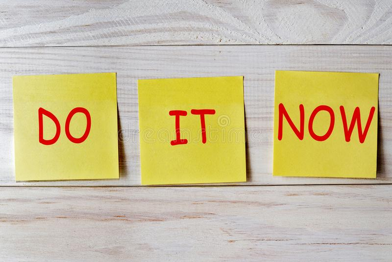 Do it now written on sticky note on wooden background.  royalty free stock photo