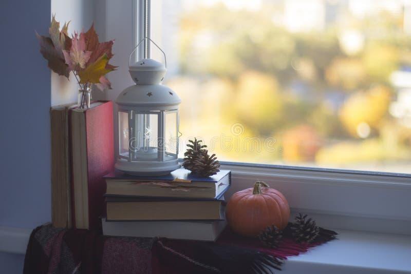 Do outono vida ainda em um peitoril da janela Pilha dos livros, da manta, da abóbora, da lâmpada, das folhas e dos cones fotografia de stock