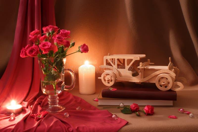 Do rosa vida bege ainda com rosas, velas e carro do vintage imagem de stock