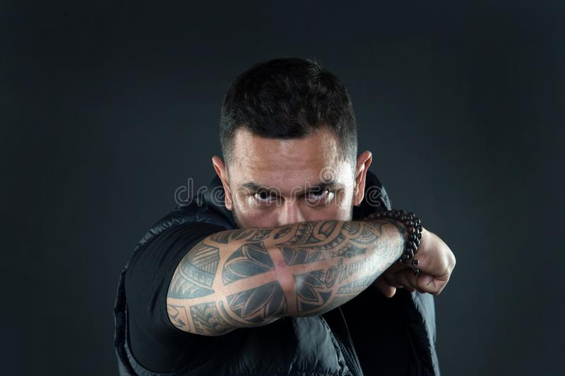 Do tattoos hide lack of masculinity. Man brutal guy cover face with tattooed arm. Tattooed elbow hide male face dark. Background. Visual culture concept. Tattoo royalty free stock photography