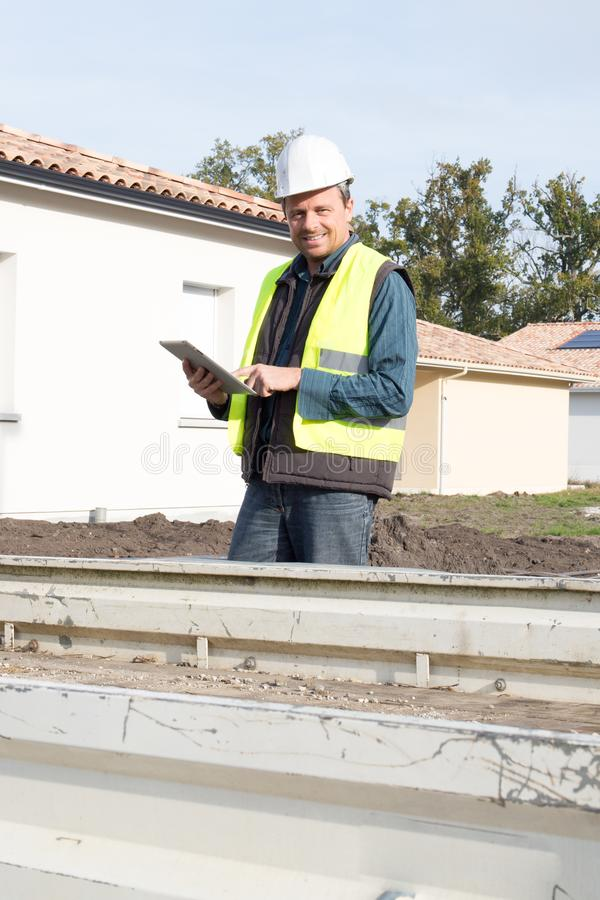 do trabalhador atrativo do contramestre do homem tabuleta de supervisão da construção que veste fora o capacete da construção imagem de stock royalty free