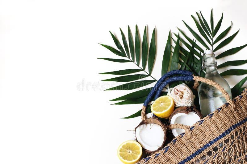 Do ver?o composi??o da vida ainda com o saco da cesta da palha, garrafa lux?ria das folhas de palmeira, dos lim?es, do coco e a d fotografia de stock royalty free