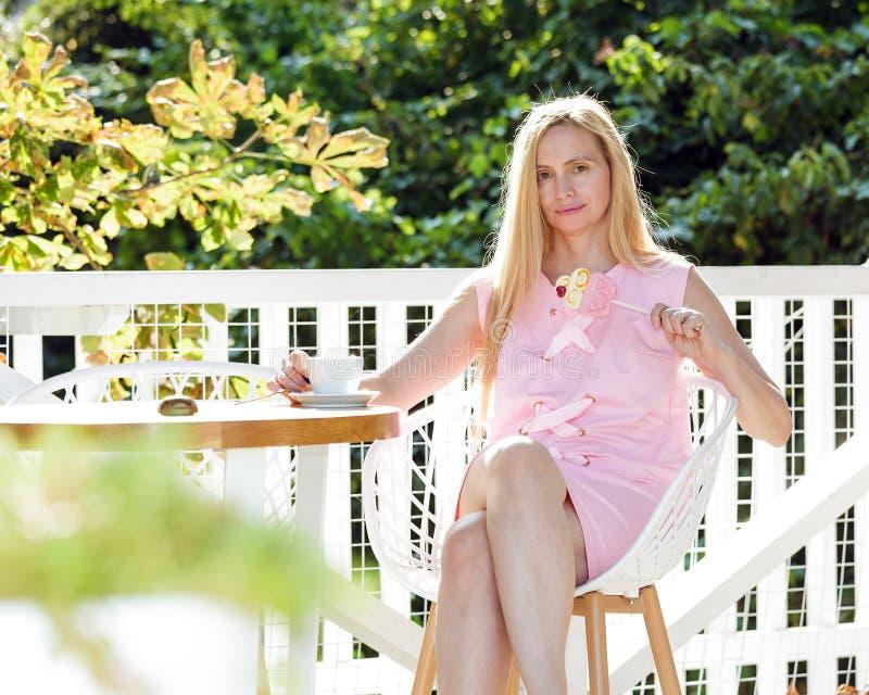 Do verão louro feliz da natureza da Idade Média da mulher da menopausa luz solar longa cinqüênta do cabelo mais a roupa cor-de-ro imagens de stock royalty free