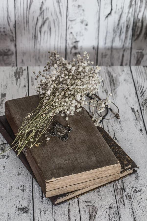 Do vintage vida ainda - os livros, os vidros e o branco secaram flores fotos de stock royalty free