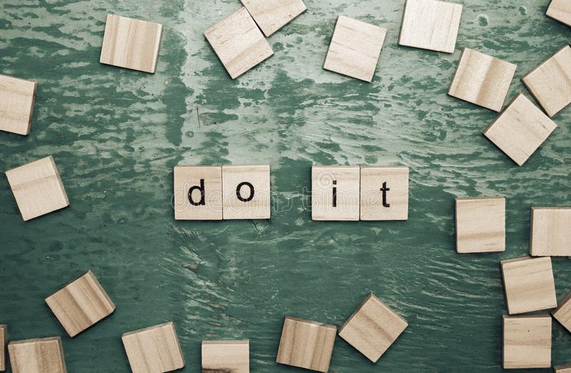 Do it words laid out with wooden letters royalty free stock photos