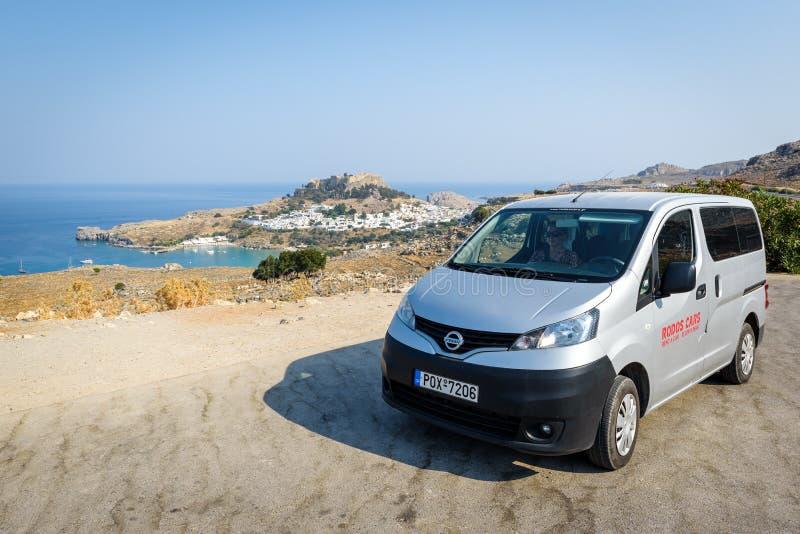 Do wynajęcia Nissan Evalia zostaje parkował blisko Lindos miasteczka na Rhodes miasteczku, Grecja obrazy royalty free