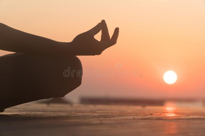Do yoga at dawn. lotus position in the sun. The sun and the girl's hand stock images