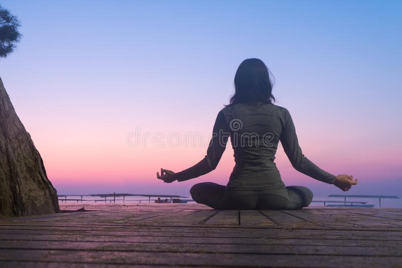 Do yoga at dawn. lotus position in the sun. Sit in lotus position at sunrise royalty free stock photo
