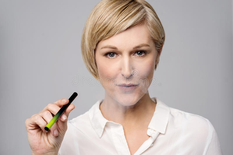 Do you like to smoke ?. Mid woman smoking modern e-cigarette stock photography