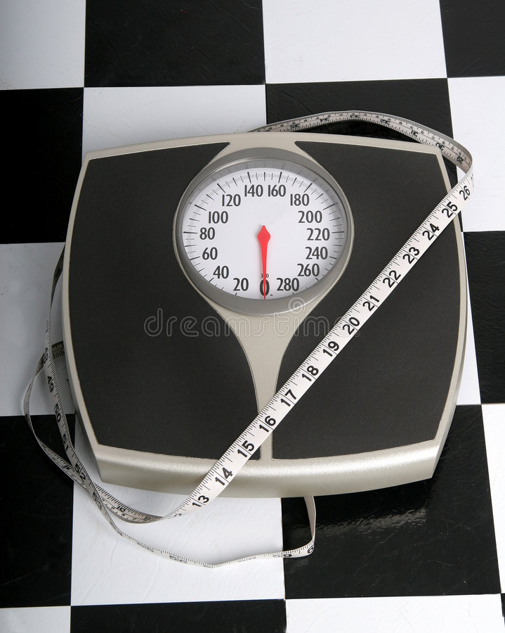 Do you measure up?. Measuring tape wrapped around scale on black and white bathroom floor stock photo