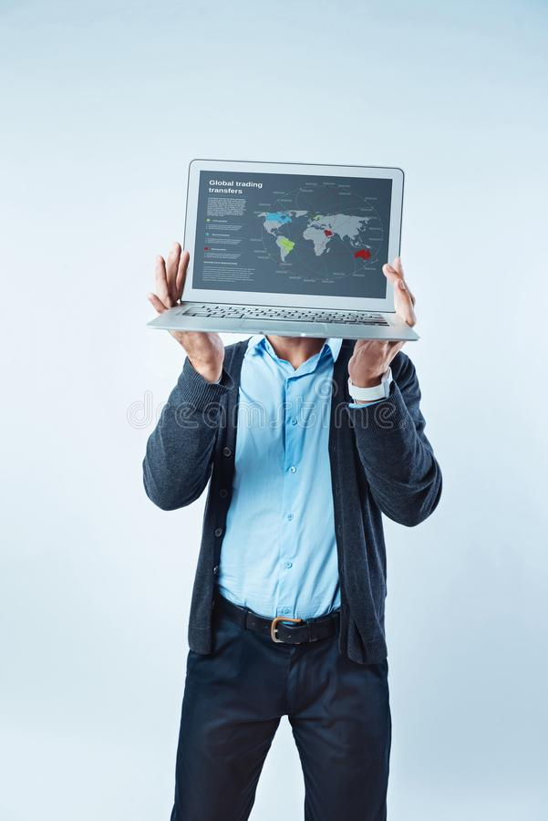 Male entrepreneur showing global trading transferring map on laptop. Do you see. Cropped shot of a male businessman hiding his face over the laptop raised in his stock photos