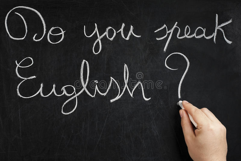 Do you speak English Hand Writing Blackboard. Do you speak English question handwritten on used chalkboard by male hand holding white chalk. Please visit my stock image