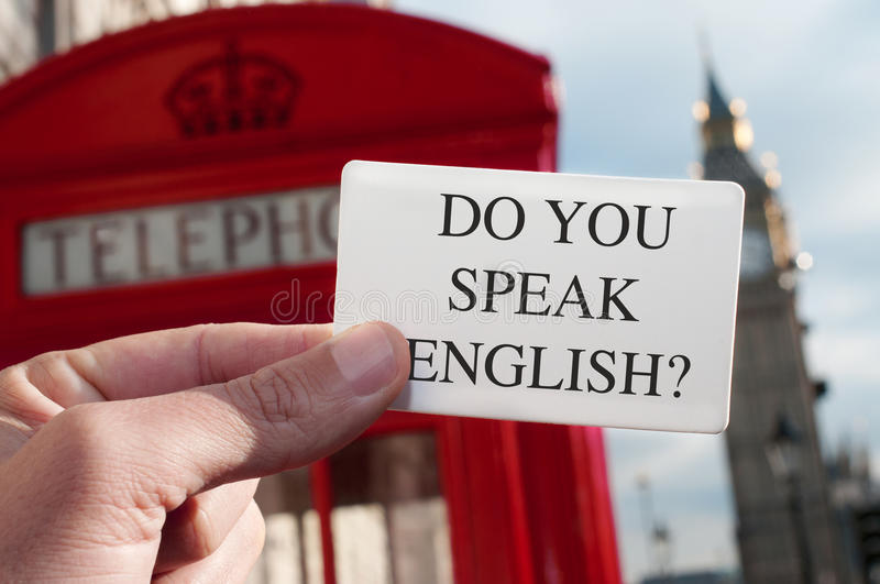 Do you speak english? in a signboard with the Big Ben in the background. A man holding a signboard with the text do you speak english? with a red telephone booth royalty free stock photos