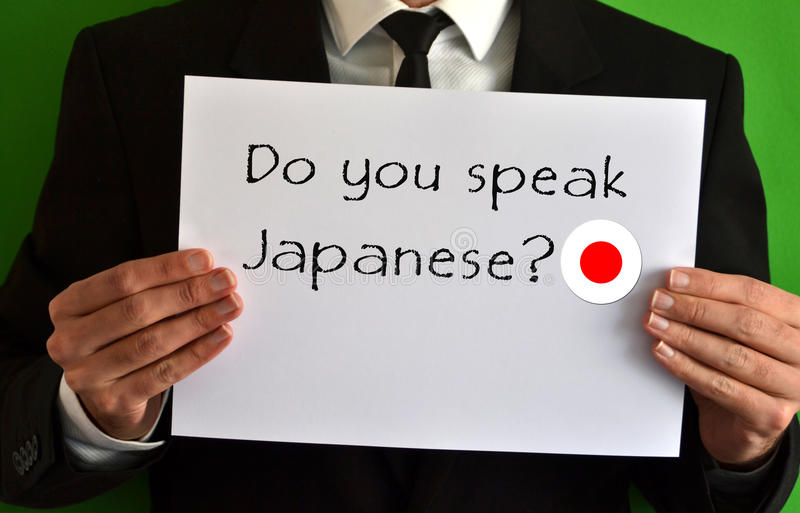 Do you speak Japanese. Businessman showing a sheet with text Do you speak Japanese royalty free stock photography