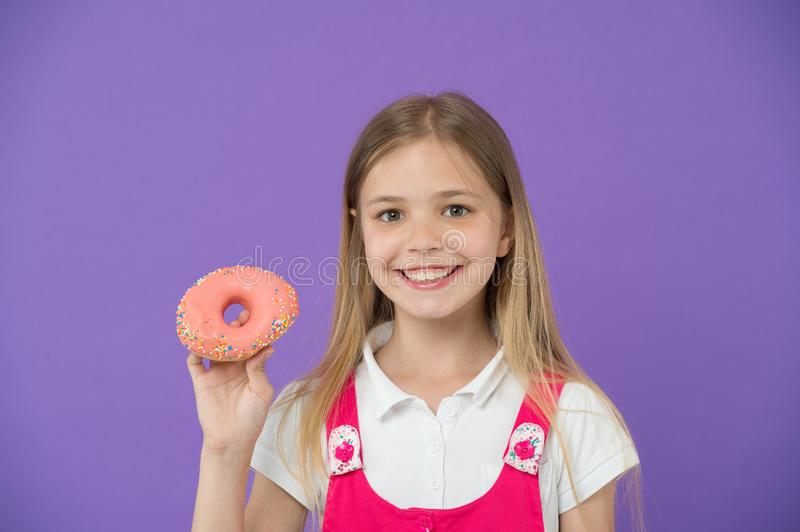 Do you want bite. Girl smiling face holds pink donut in hand, violet background. Kid smiling girl ready to bite donut stock photo