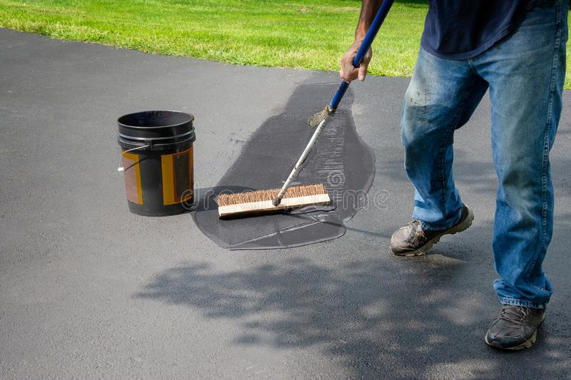 Spreading asphalt in home driveway. Do it yourself home maintenance. Driveway resealing repair. Homeowner spreads blacktop sealant stock images