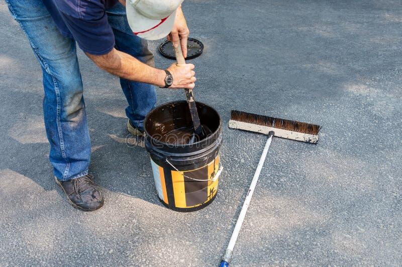 Driveway maintenance, stirring sealant before pouring. Do it yourself home maintenance. Driveway resealing repair. Man stirs pail of sealant before using on stock image