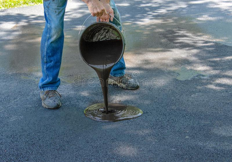 Pouring asphalt sealant on driveway. Do it yourself home maintenance. Driveway resealing repair. Pouring asphalt onto driveway from a bucket royalty free stock photo