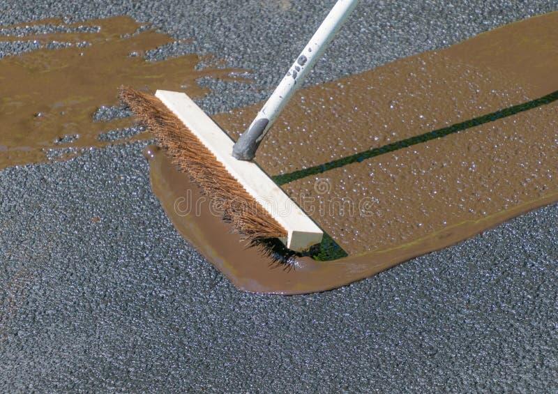 Driveway maintenance, spreading sealant. Do it yourself home maintenance. Driveway resealing repair. Spreading sealant to coat asphalt stock photography