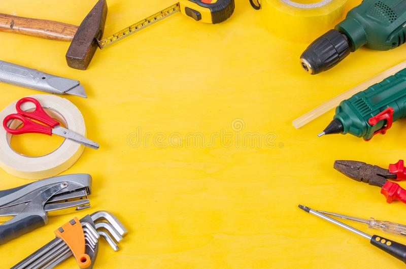 Do it yourself tools on yellow background. DIY tools with copy space for text on yellow wooden background. Different tools for han royalty free stock photos