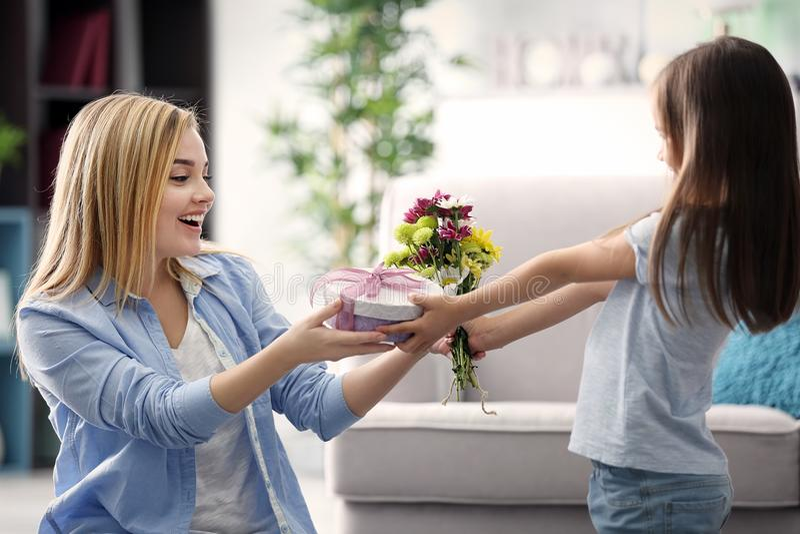 Doação da menina atual a sua mãe em casa fotografia de stock