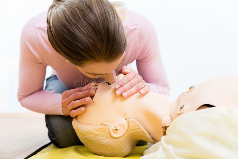 Doação da respiração da boca-à-boca do treinamento da mulher no manequim imagens de stock