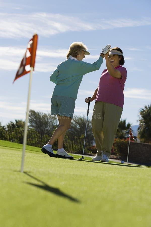 Doação de duas mulheres elevada-cinco no campo de golfe imagens de stock royalty free
