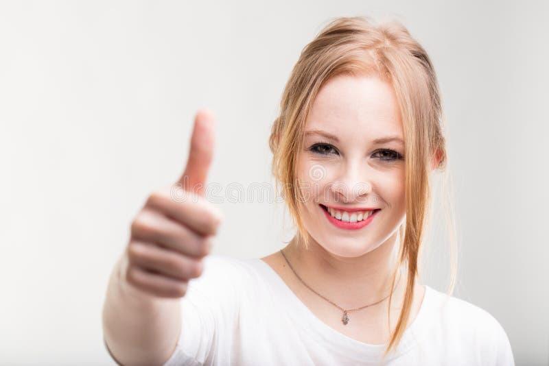 Doação de sorriso da jovem mulher polegares acima fotos de stock