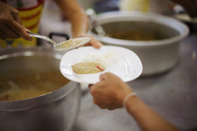 Doação do alimento na comunidade pobre dos voluntários: Conceito social da partilha pobre dos povos imagens de stock royalty free