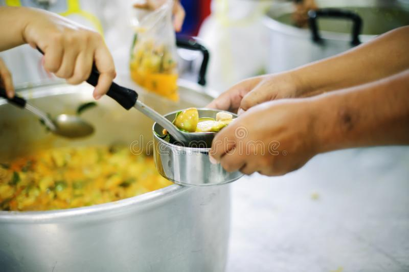 Doação do alimento na comunidade pobre dos voluntários: Conceito social da partilha pobre dos povos imagens de stock