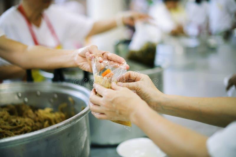 Doação do alimento na comunidade pobre dos voluntários: Conceito social da partilha pobre dos povos imagem de stock