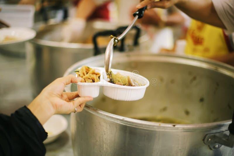 Doação do alimento na comunidade pobre dos voluntários: Conceito social da partilha pobre dos povos fotos de stock