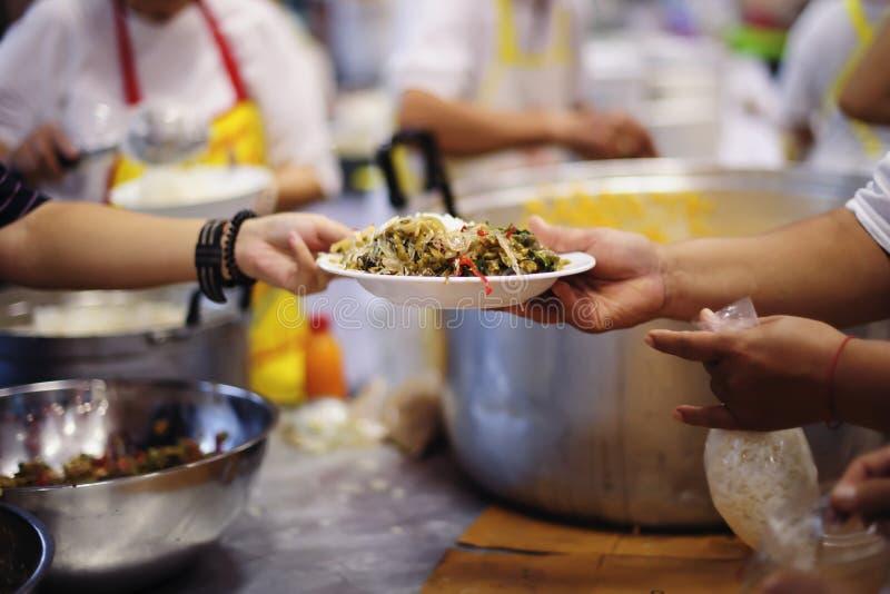 Doação do alimento na comunidade pobre dos voluntários: Conceito social da partilha pobre dos povos foto de stock royalty free