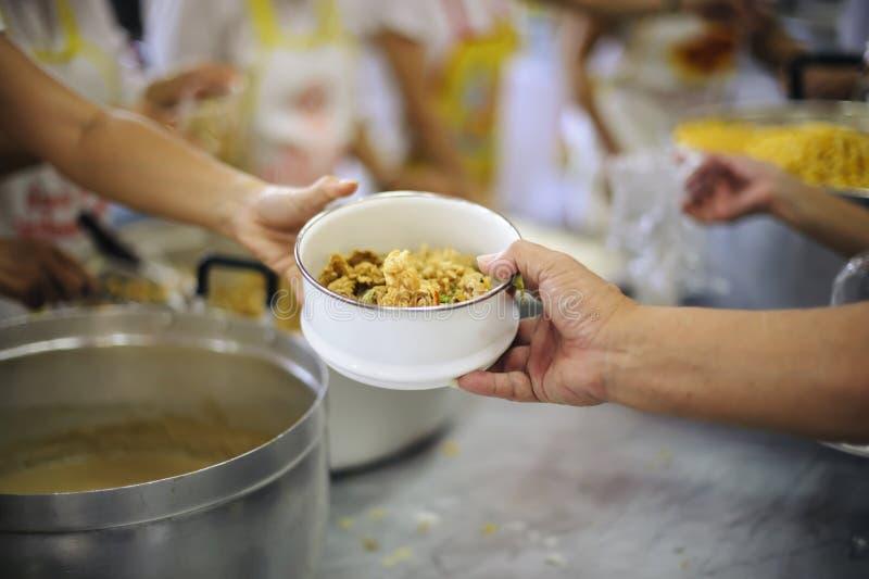 Doação do alimento na comunidade pobre dos voluntários: Conceito social da partilha pobre dos povos fotos de stock royalty free