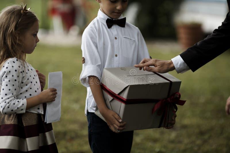 Doação do pai atual ao filho Menino de sorriso feliz que recebe um presente Família feliz, aniversário, ano novo, conceito do Nat imagens de stock royalty free