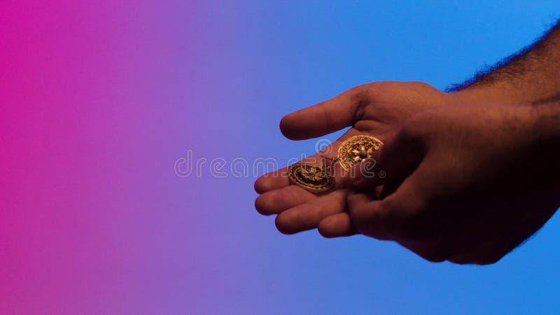 Doação fêmea das mãos do mehendi dourada, oriental, brincos feitos a mão em um fundo colorido, joia antiga do vintage fotografia de stock royalty free