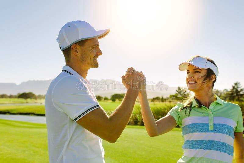 Doação masculina e fêmea dos amigos alta-cinco no campo de golfe fotografia de stock royalty free