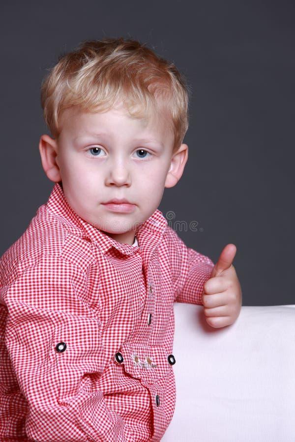 A doação nova do menino os polegares levanta o gesto foto de stock