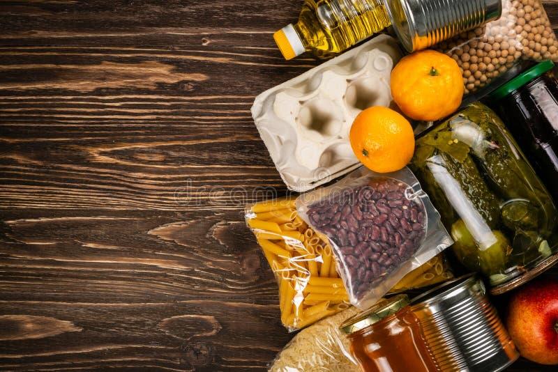 Doações do alimento na caixa no fundo da cozinha imagem de stock