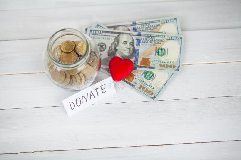 Doações e caridade Conceito da doação Vidro com doações no fundo branco A inscrição doa Caridade e dinheiro imagem de stock