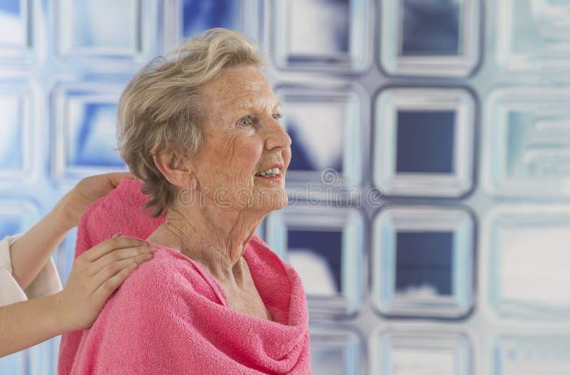 Doador ou enfermeira de cuidado que ajudam à mulher idosa para o chuveiro imagem de stock royalty free