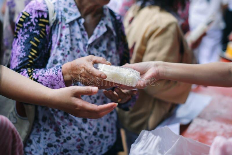 Doar o alimento está ajudando amigos humanos na sociedade: Povos de ajuda com fome com bondade: o conceito de problemas da vida, imagem de stock royalty free