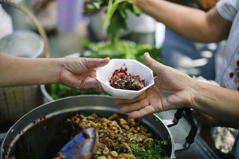 Doar o alimento está ajudando amigos humanos na sociedade: Povos de ajuda com fome com bondade: o conceito de problemas da vida, fotografia de stock royalty free