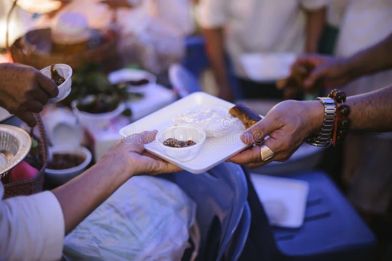 Doar o alimento está ajudando amigos humanos na sociedade: Povos de ajuda com fome com bondade: o conceito de problemas da vida, imagens de stock royalty free