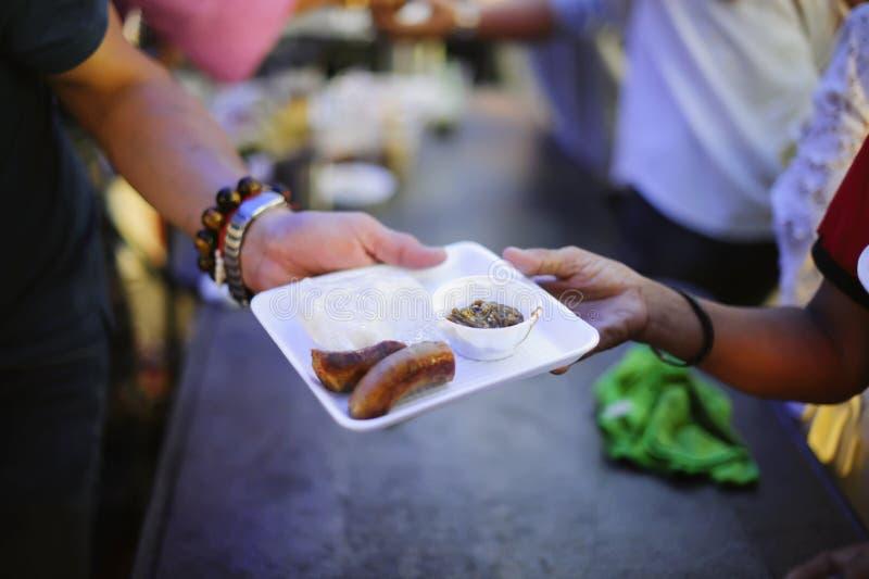 Doar o alimento está ajudando amigos humanos na sociedade: Povos de ajuda com fome com bondade: o conceito de problemas da vida, foto de stock royalty free